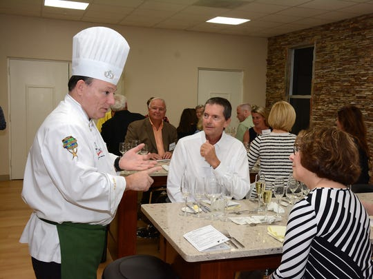 Chef Ralph Ferco discusses the upcoming course with guests, including Joe Balavage.