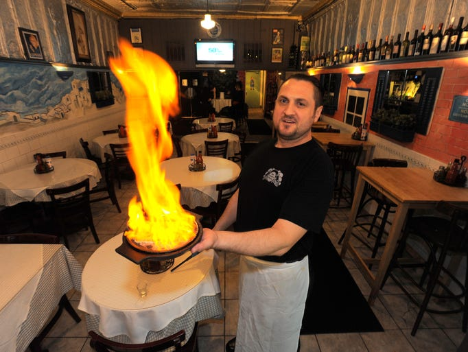 Vaso Nikprelaj lights up a dish of saganaki, a fried