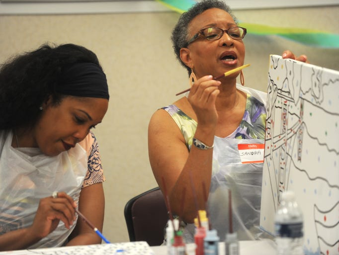 Sandra Tomlin, right, of Detroit, works on her painting