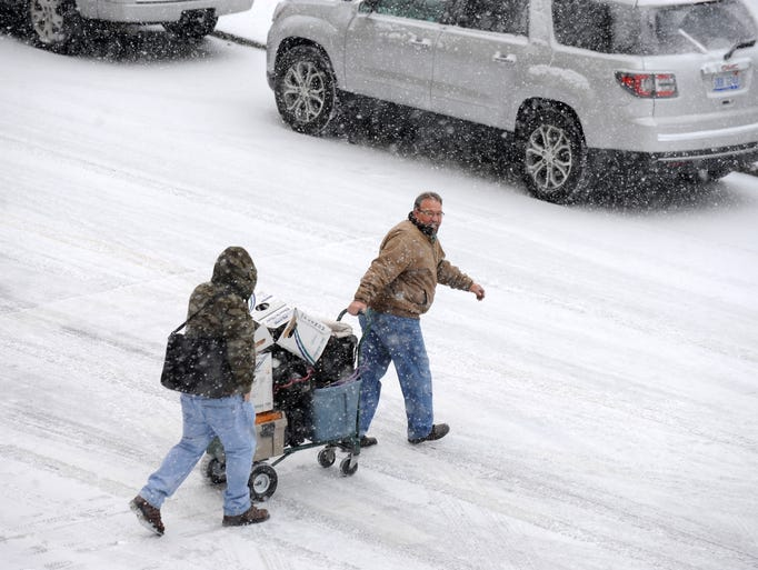 A cart is navigated through snowy Detroit streets Wednesday,