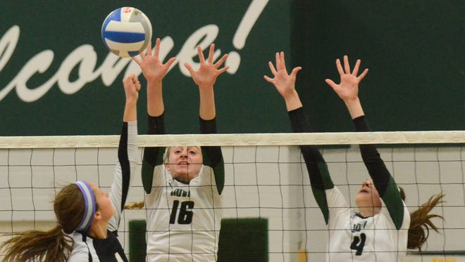 Novi's Ally Cummings (middle) and Emmy Robinson (right) team up to block the shot of Grosse Pointe North's Mackenzie Simon.