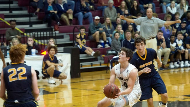 Navarre point guard Matthew Harshany makes a move and looks up the court for a scoring opportunity. Harshany's play has been instrumental for the Navarre Raiders this season.