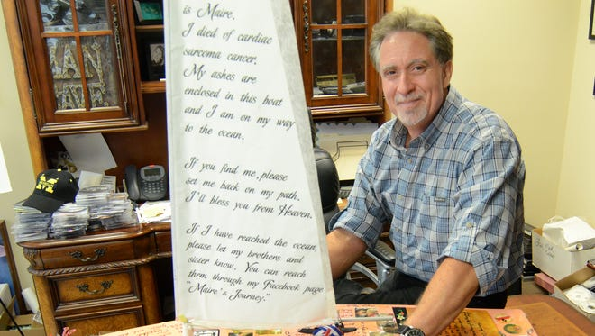 In his Wixom office, documentary filmmaker Keith Famie shows the small sailboat that carried the ashes of Maire Kent from the Great Lakes to the Atlantic Ocean.