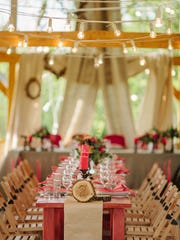 Chairs and table  decorated with candles and flowers.