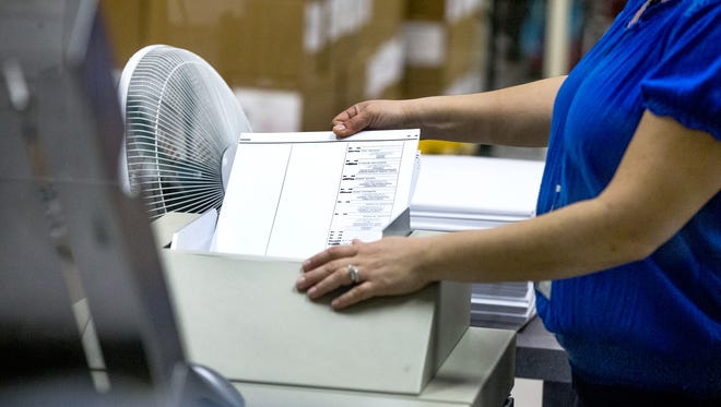 Renee Suaava runs ballots through a machine as election workers conduct a recount at the Maricopa County Elections Department in Phoenix on Sept. 13, 2016.