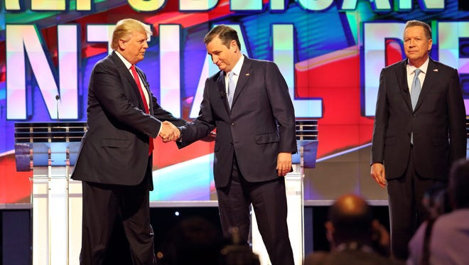 Donald Trump and Ted Cruz shake hands as John Kasich looks on during the Republican debate in Miami on March 10, 2016.