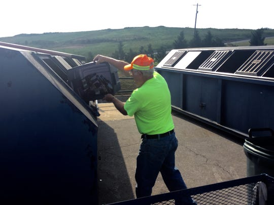 Gary Thomas dumps bottles into a holding bin for glass recycling at the Pickens County landfill and recycling center.