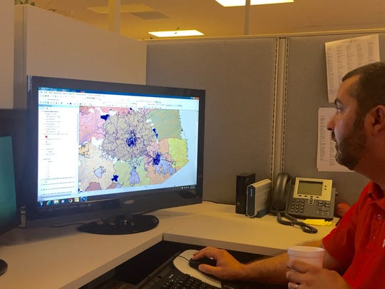 Jimmy Threatt, Pickens County's Geographic Information Systems specialist, works with a map showing fire district coverage.