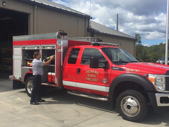 Firefighter Anthony Still checks equipment on a truck at the Concord Road station, one of Pickens County's new fire stations.