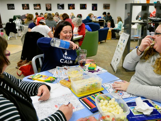 Patty Burkhardt of West Manchester Township, center, refills a glass of wine for her cousin Krystalyn Carson of West Manchester Township as they color with Burkhardt's mother Kim McClaskey of Mount Joy, left, and friend Carrie Brickner of West Manchester Township, not pictured, during the seventh Coloring and Cocktails event.