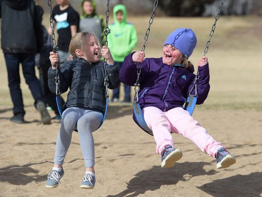 Audrey Sherman, left, and Samara Chesser swing during