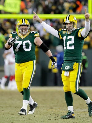 Green Bay Packers quarterback Aaron Rodgers (12) celebrates after throwing a Hail Mary for a touchdown as time expired in the second quarter against the New York Giants at Lambeau Field.