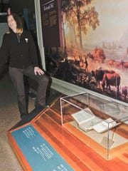 In this Dec. 1, 2016 photo, National Historic Oregon Trail Interpretive Center Director Sarah LeCompte stands next to the J.C. Fremont book exhibit in the Center in Baker City, Ore. Through a partnership between the Library of Congress and the office of Sen. Ron Wyden, D-Ore., the 170-year-old, seven-section topographical map of the Oregon Trail that is bound into a book, has been secured for display at the Center. (S. John Collins/Baker City Herald via AP)