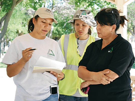 Groundwork Doña Ana Supervisor Viridiana Arellano reviews data she's collected with GWDA Executive Director Ceci Vasconcellos, right, and another GWDA worker.