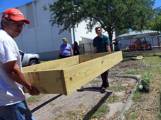 Benny Prado (right) and County Extension Agent Kevin Gibbs from Texas A&M AgriLife prepare an area to plant vegetables and flowers at a community garden on Monday, April 3, 2017, at the YWCA in Corpus Christi.