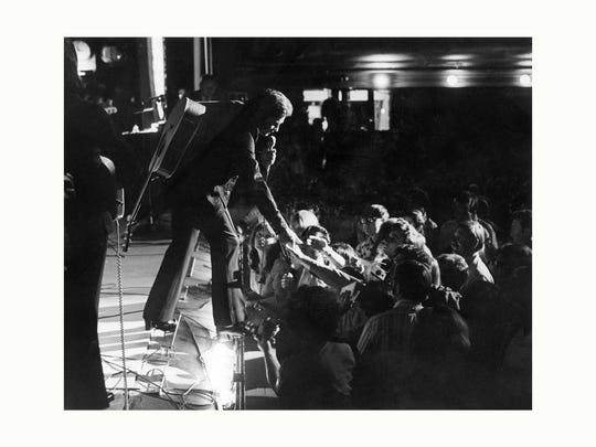 """Johnny Cash steps over the footlights, extending welcoming handshakes to fans at the """"Grand Ole Gospel Time"""" show that followed the Friday night Opry. The show was hosted by Hank Snow's son, Pastor Jimmie Snow, and Cash was one of the first guests."""