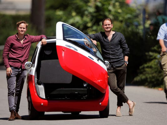 Oliver and Merlin Ouboter of Swiss Microlino AG pose beside an electric-powered Microlino car in Kuesnacht
