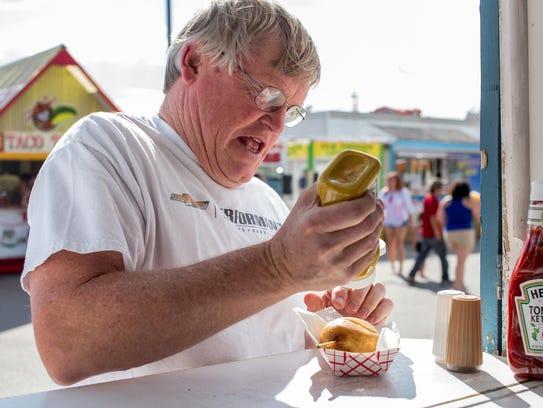 Gary Gebo puts mustard on his fresh Viking at the Montana