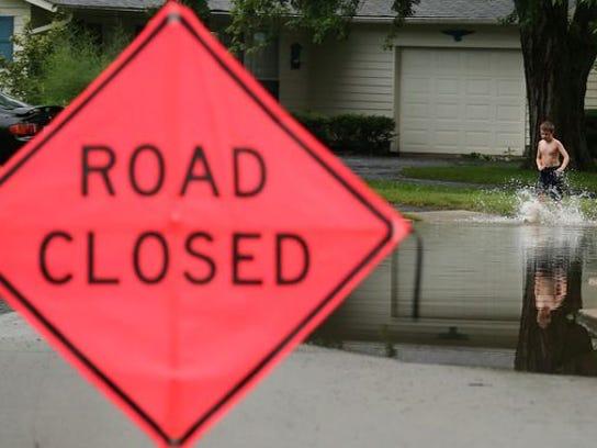 Matthew LaFollette, 9, wades through flooding along Emerson Road in Carmel on Thursday.