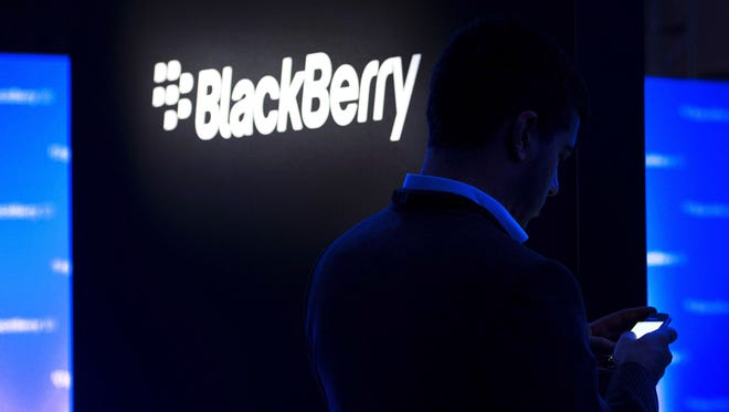 A man uses his Blackberry as people wait for the Blackberry BB10 launch in Toronto last year.
