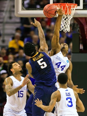 Kentucky's Dakari Johnson blocks the shot of West Virginia's Devin Williams in the second half during Thursday evening's Sweet 16 game in Cleveland. The Wildcats rolled past the Mountaineers 78-39. March 26, 2015.