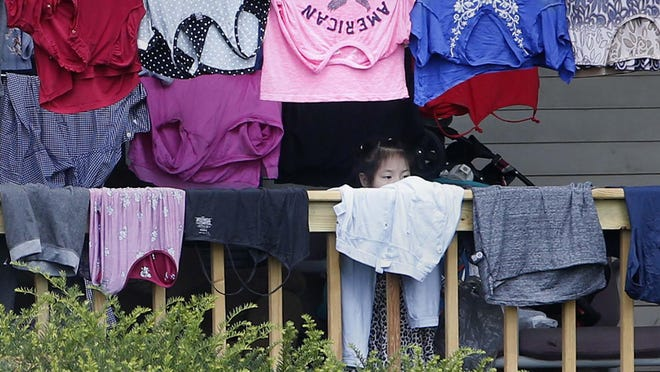 A young girl peers over clothes hanging out to dry in an Akron neighborhood that is home to many Bhutanese Nepalis, who came to America as refugees in recent years. Many work in meatpacking plants and have been disproportionately affected by the pandemic.