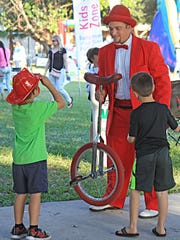 Entertainer Azriel Loschak discusses his unicycle with a few young fans at Jupiter Jubliee.