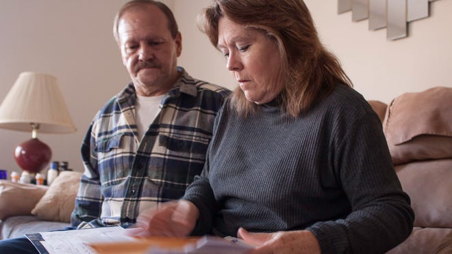 Penelope Adams and her husband, Donald, look through past due statements from the hospital at their home in Bethel Springs. Adams suffered from a ruptured colon and went into debt. Her doctor would not see her without payment, and she traveled to Mississippi to complete her surgery.