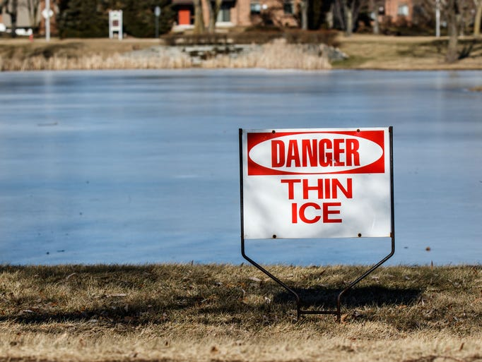 Pedestrians are reminded of thin ice near a pond in