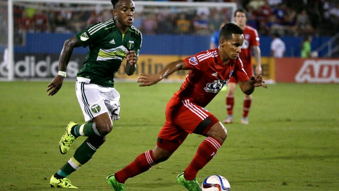 FC Dallas midfielder Michael Barrios, right, gets past Portland Timbers defender Rodney Wallace (22) during the second half of an MLS soccer game in Frisco, Texas, Saturday, July 25, 2015. FC Dallas won 4-1.