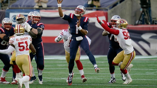 New England Patriots quarterback Cam Newton, center, passes under pressure from San Francisco 49ers linebacker Azeez Al-Shaair (51) and defensive end Dion Jordan, right, in the first half of an NFL football game, Sunday, Oct. 25, 2020, in Foxborough, Mass.