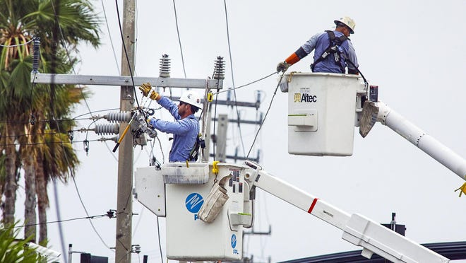 Workers from Florida Power & Light repair a broken power line on North County Road near Sunset Avenue in Palm Beach as winds from Isaias pass by the area Sunday morning.