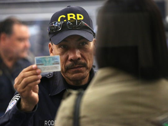 Un oficial del CBP inspecciona la identidad de una mujer que busca cruzar hacia EU.
