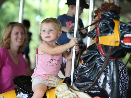 Ashtyn Stanley, 2, along with her mom, Terra, ride the Grand Carousel at Kings Island in Mason.