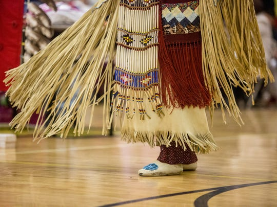 Ornate regalia sways the the movement of a dancer during a traditional dance at the Algonac American Indian Festival and Powwow Saturday, April 30, 2016 at Algonac High School.