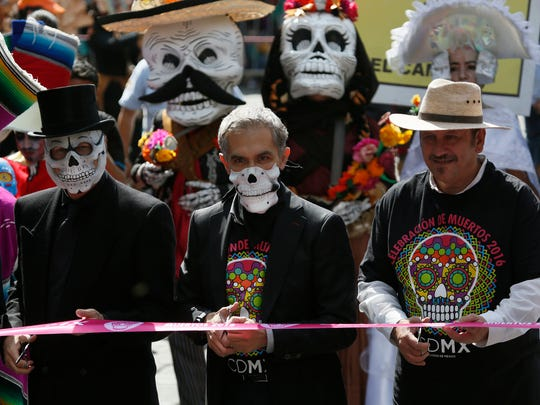 Mexico City Mayor Miguel Angel Mancera, center, cuts the ribbon to inaugurate the city's first Day of the Dead parade in Mexico City, Saturday, Oct. 29, 2016. Hollywood movies, zombie shows, Halloween and even politics are fast changing Mexico's Day of the Dead celebrations, which traditionally consisted of quiet family gatherings at the graves of their departed loved ones bringing them music, drink and conversation.
