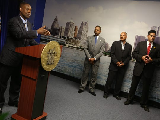 Detroit Emergency Financial Manager Kevyn Orr, left annouces that he  filled for municipal bankruptcy during a press conference at the Coleman A. Young municipal building in Detroit on Thursday, July 18, 2013.