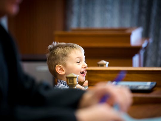Thu., Jan. 25, 2018: Lucas, 2, smiles at his friends and family from behind Hamilton County Judge Ralph Winkler's bench. Winkler said he always suggests that parents let their kids run during proceedings, and so Lucas made laps around the courtroom. Cameron and Jennifer Knight have fostered several children over the last two years, and Lucas is their first adoption. The Enquirer/Carrie Cochran