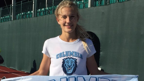 Natalie Tanner stands with Columbia Lions flag after