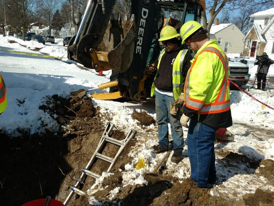 BWL lead service replacement crew members assist with a lead pipe replacement in Flint in 2016.