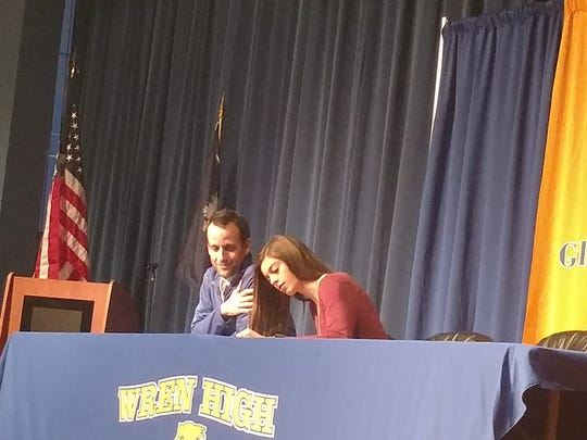 Ashlyn Little, right, signs a national letter of intent Monday during a signing ceremony at the school while head coach Matthew Truesdale looks on.