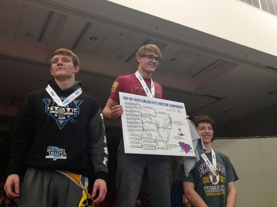 Powdersville's Liam McKinney celebrates atop the podium after winning the Class AAA 160-pound state championship.