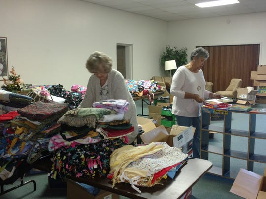 Mary Lou Beard, left, and the Rev. Frances Gonzalez sort the items that Beard brought from Ohio to benefit people in need in Fabens.