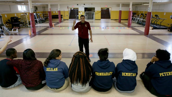 Students at the Rochester Academy Charter School listen to teacher Rich Vleck in a makeshift gym in the basement of the school's Portland Avenue campus.