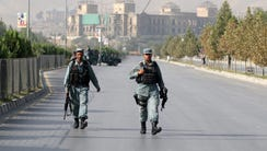 Afghan security officials secure a road leading to