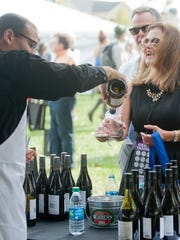 Cathy and Peter Ervin are poured a glass of wine by Benito Bedart at the 2017 Wine and Food Experience.