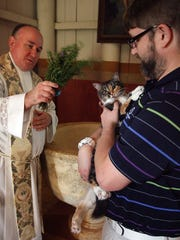 Father Craig Smith blesses Gerald Higgins' cat Bubbles during a previous Blessing of the Animals at  Mission San Luis.