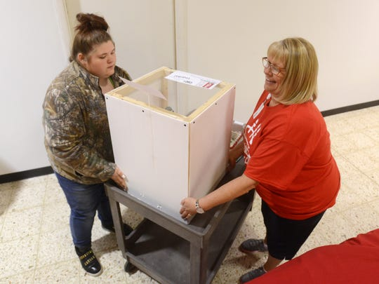 Foxfire High School volunteers Tammy Porter, right, and senior Morgan Ross lift a cake onto a cart at the Carr Center Cake Auction at Colony Square Mall on Friday. The school had 30 student volunteers at the cake auction during its two-day run.