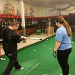 Raleigh Baseball Institute onwer and instructor Matt Raleigh shows student Alexis Cardianle the importance of staying behind the ball when hitting.