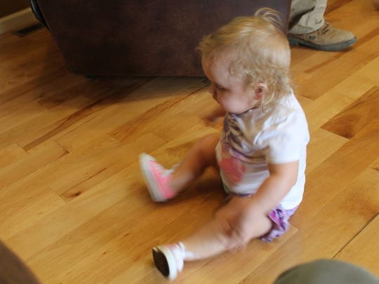 Aubrey Ferrell chases her sister by scooting across the floor. At almost two years old, she cannot walk or crawl.